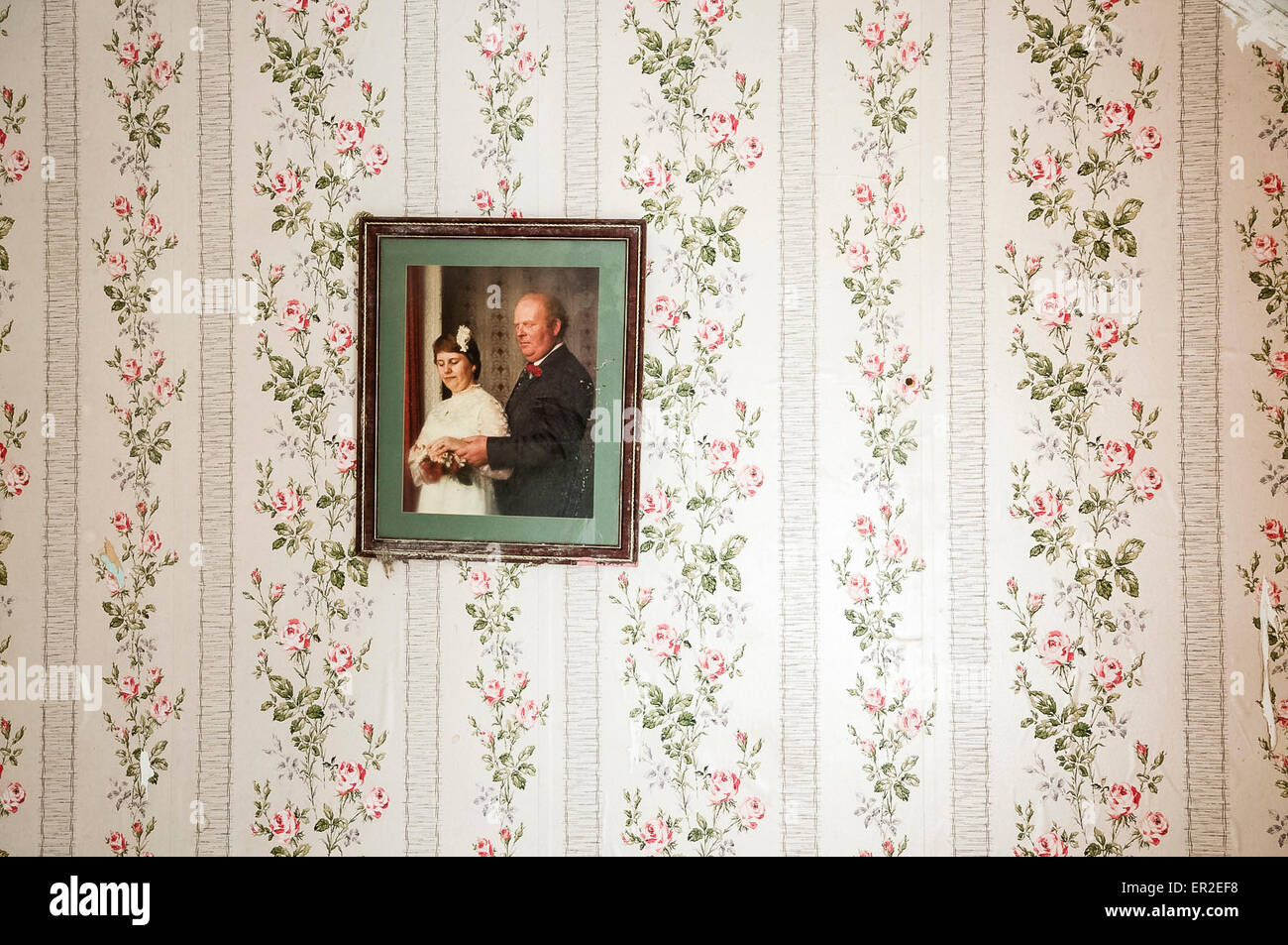 Wedding picture hanging on a wall with old fashioned floral wallpaper. - Stock Image
