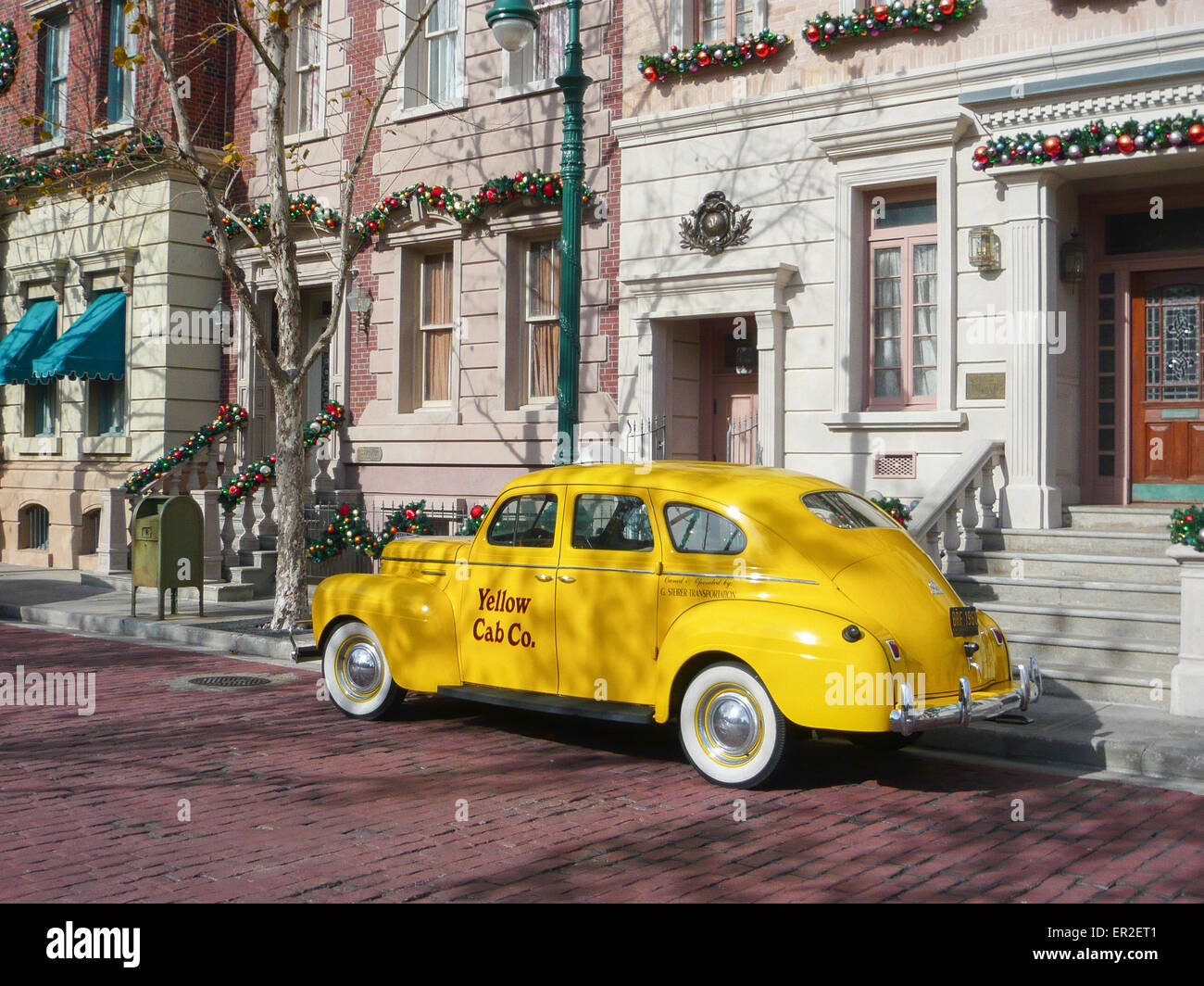 Yellow cab outside a house. - Stock Image