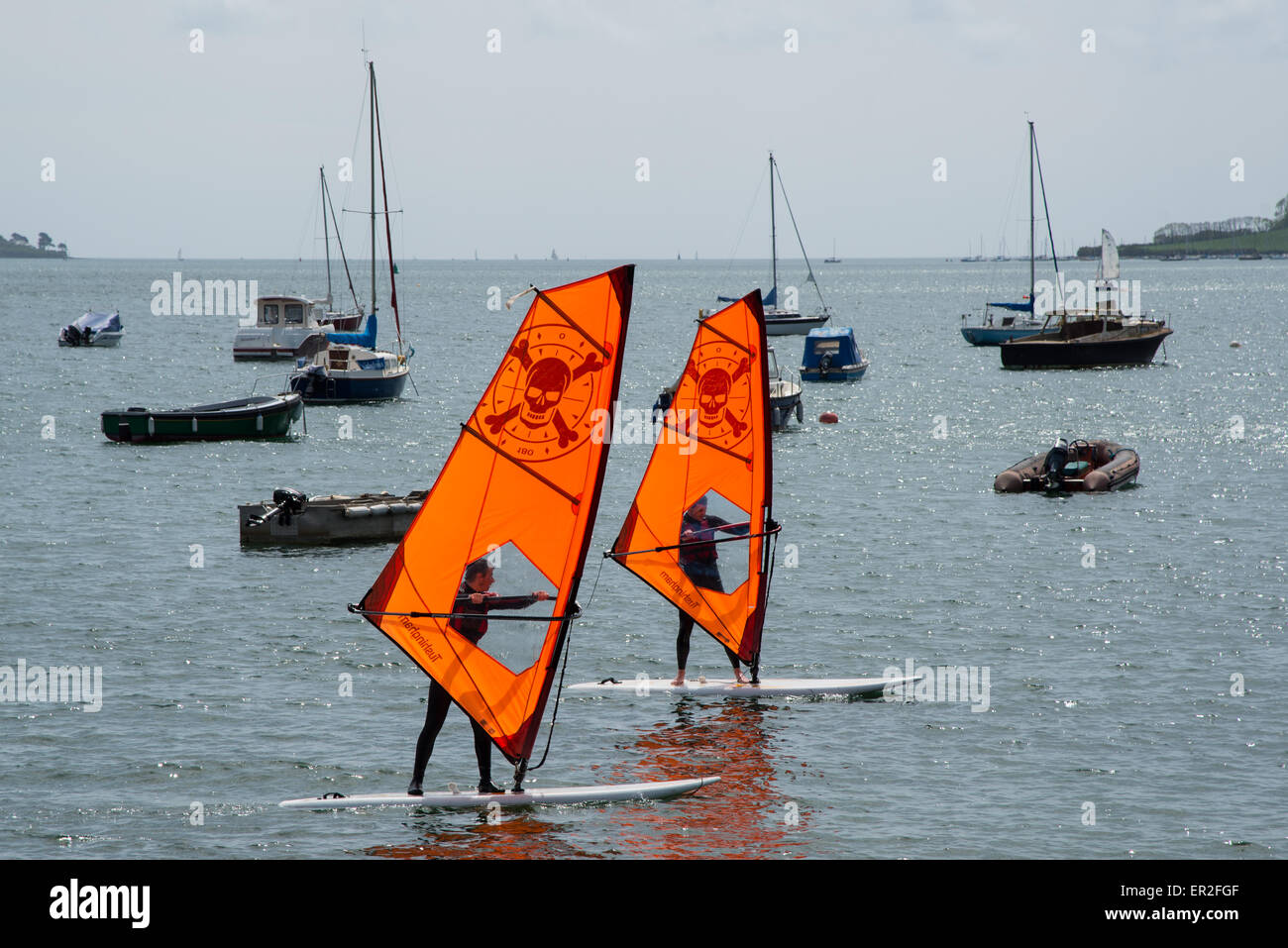 Two individuals learning to windsurf at Loe Beack, Feock near Falmouth, Cornwall. - Stock Image