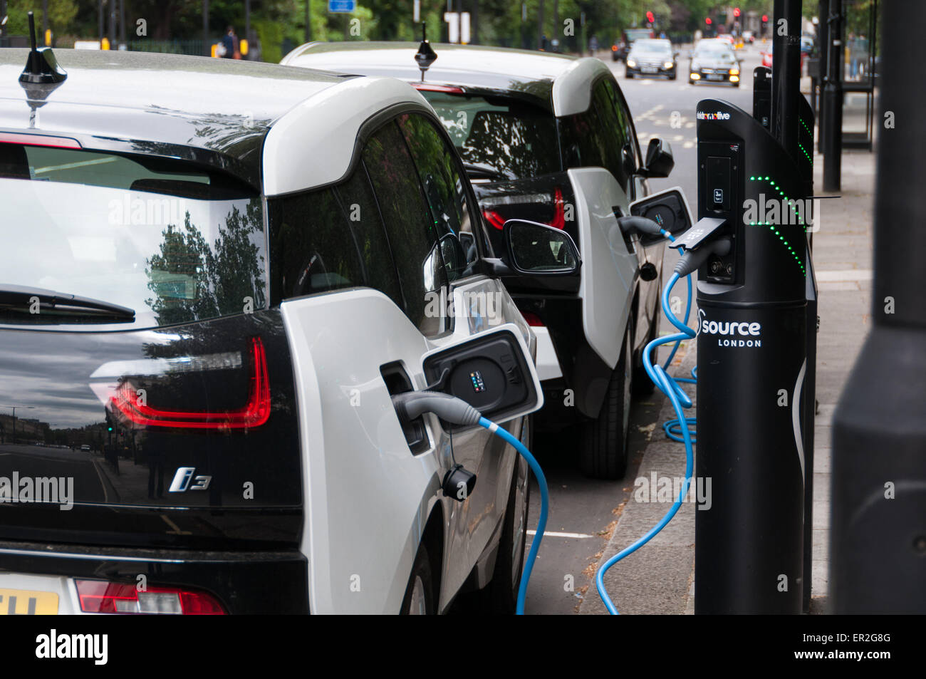 Electric BMW i3 cars plugged into electric charging bays in London, England Stock Photo