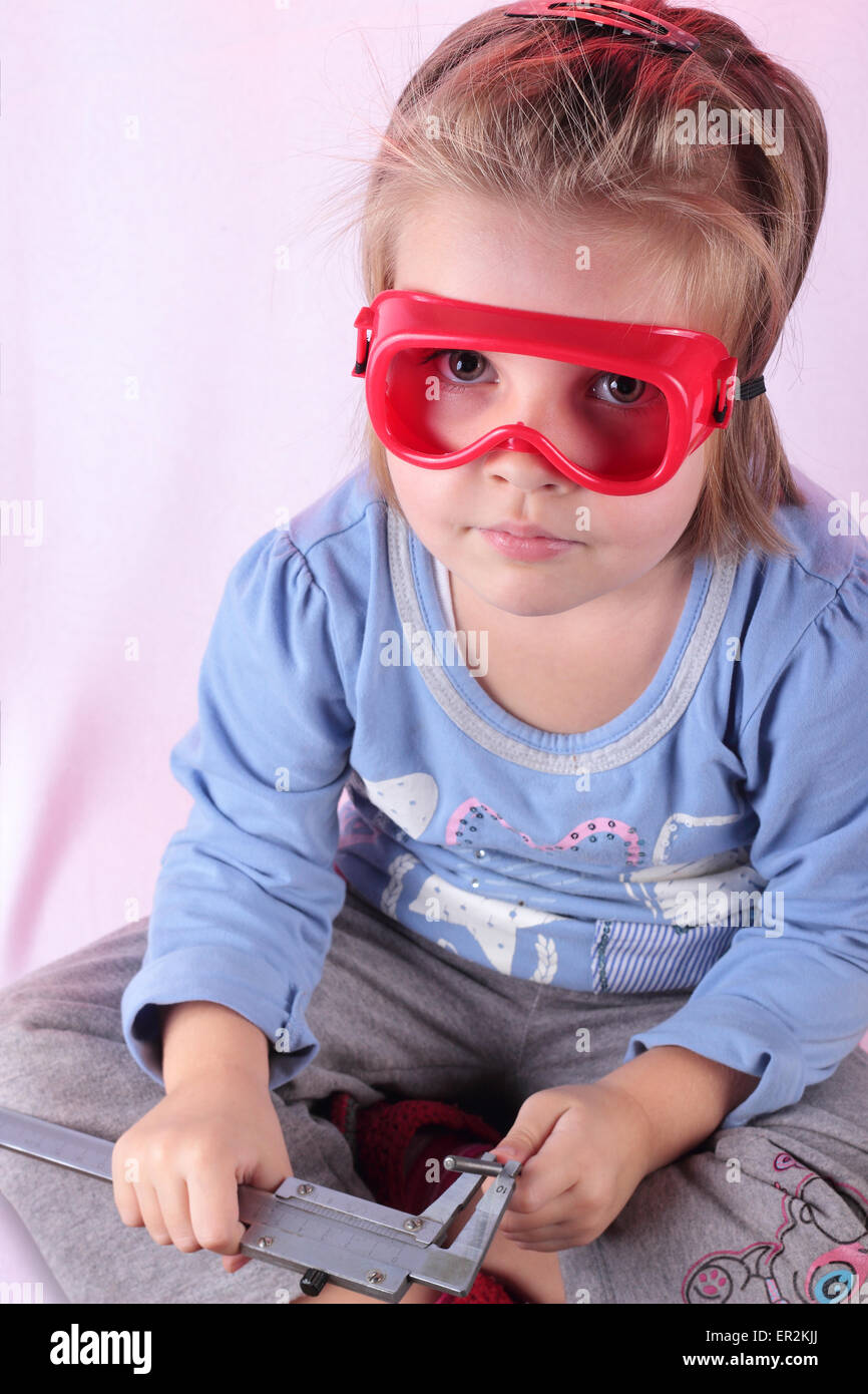 The little girl measures by a caliper diameter of a drill. - Stock Image
