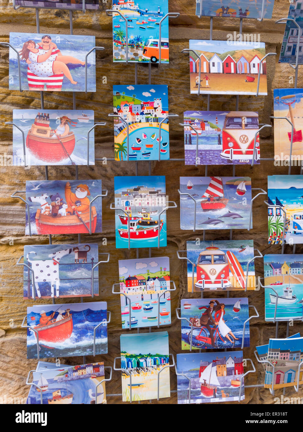 Seaside postcards for sale in a rack outside a shop in Whitby, North Yorkshire, UK - Stock Image