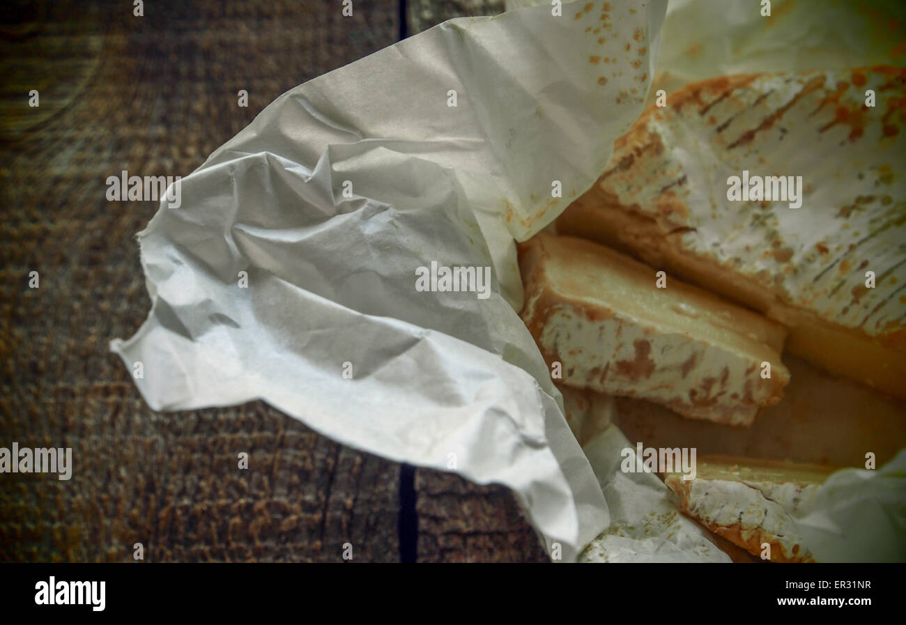 Camembert on crumpled wrapping paper on wooden background. Grunge style. 26th May, 2015. © Igor Golovniov/ZUMA - Stock Image