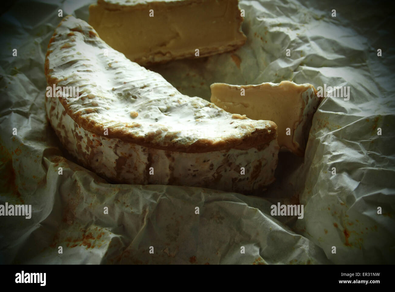 Camembert on crumpled wrapping paper. Grunge style. 26th May, 2015. © Igor Golovniov/ZUMA Wire/ZUMAPRESS.com/Alamy - Stock Image