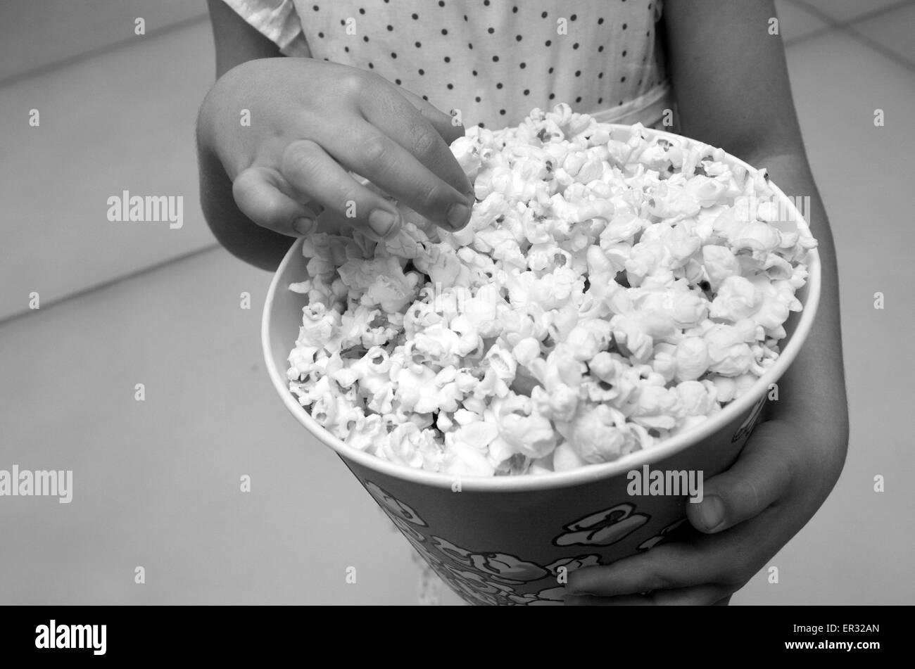 Hands of a little child (girl age 5) eats popcorn. Concept photo of children health care, healthy food  and diet - Stock Image