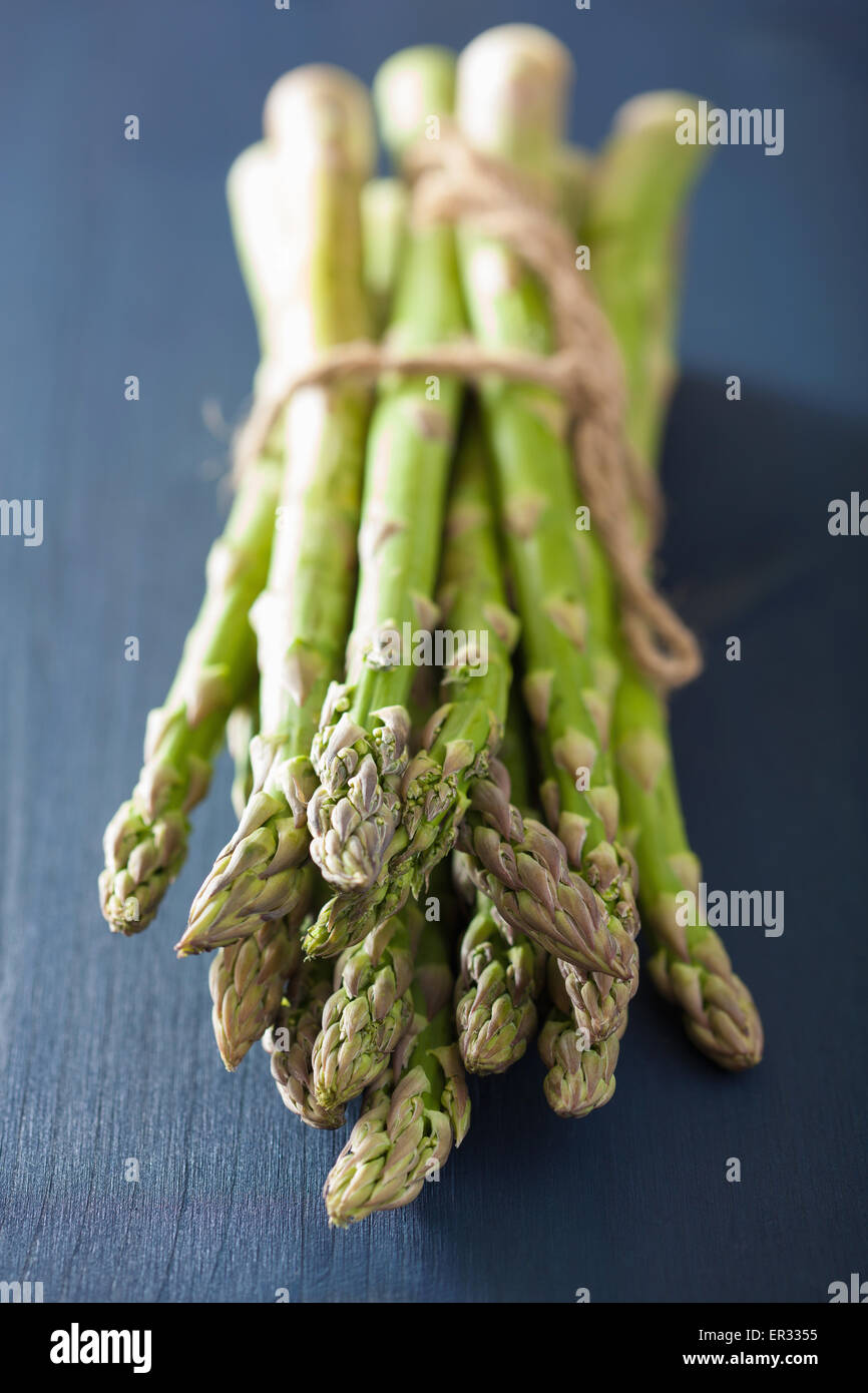 bunch of fresh asparagus on blue background - Stock Image