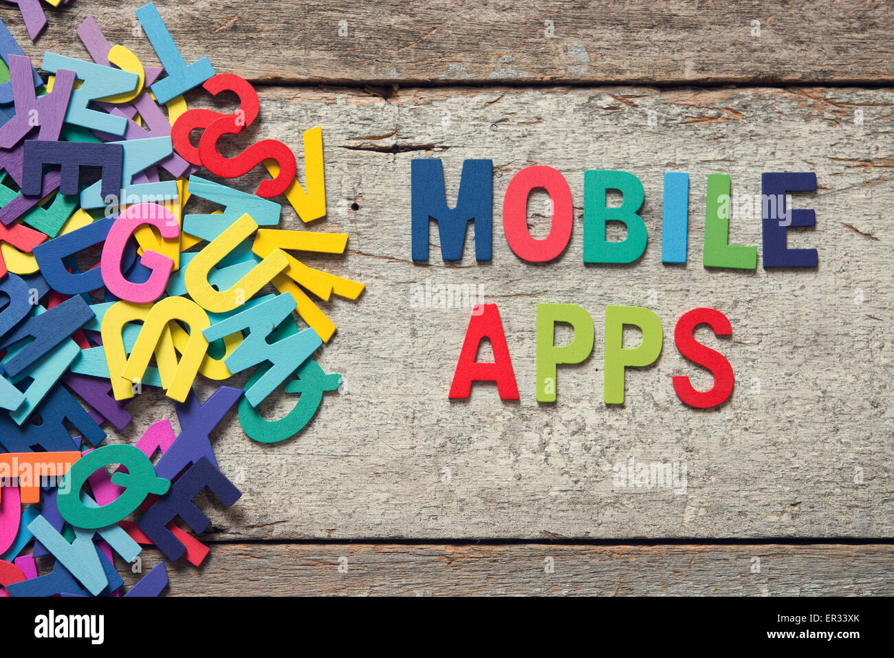 The colorful words 'MOBILE APPS' made with wooden letters next to a pile of other letters over old wooden - Stock Image