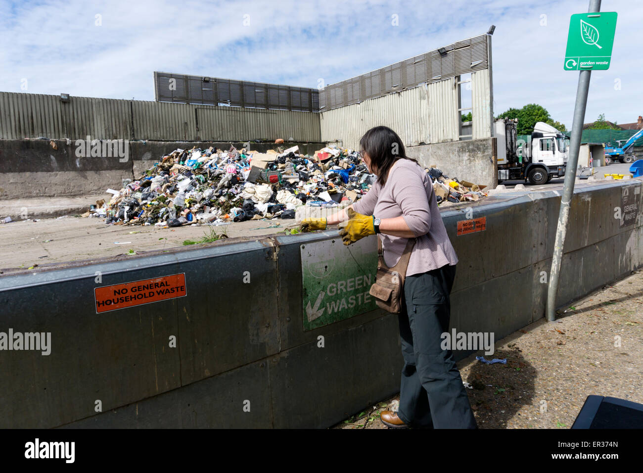 A woman dumping green garden waste at a municipal tip or recycling centre. - Stock Image