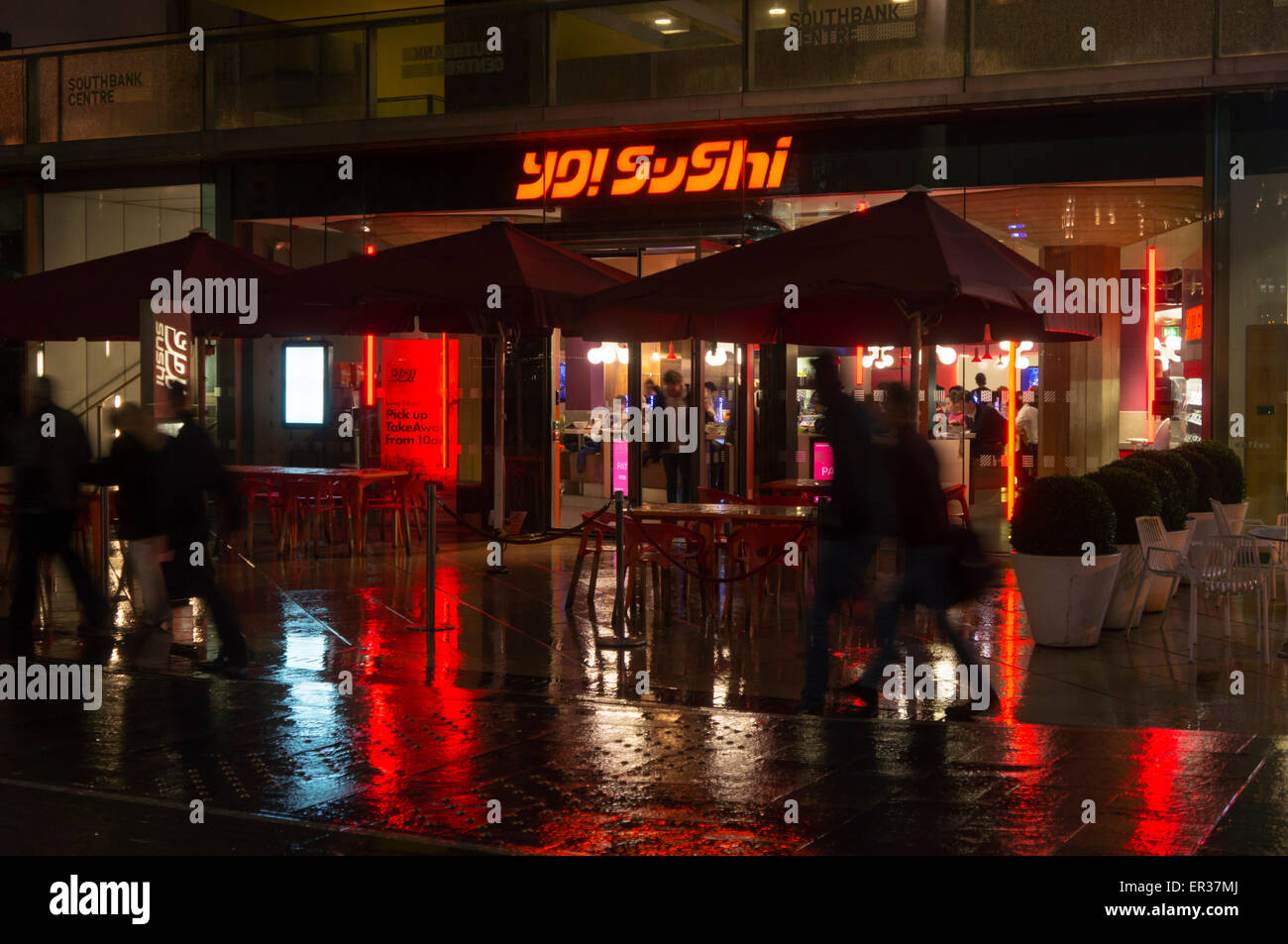 Branch of Yo! Sushi on the Southbank in London at night in the rain. - Stock Image