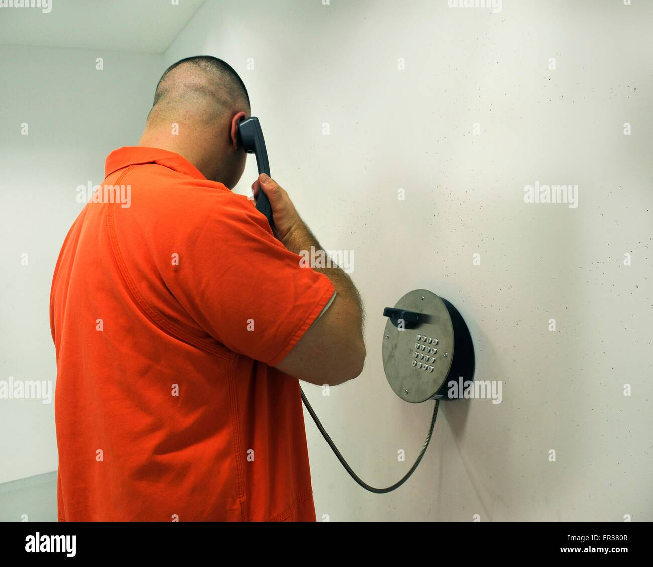 A prisoner in orange jump suit makes a phone call from inside the U.S. Army Regional Correctional Facility located - Stock Image