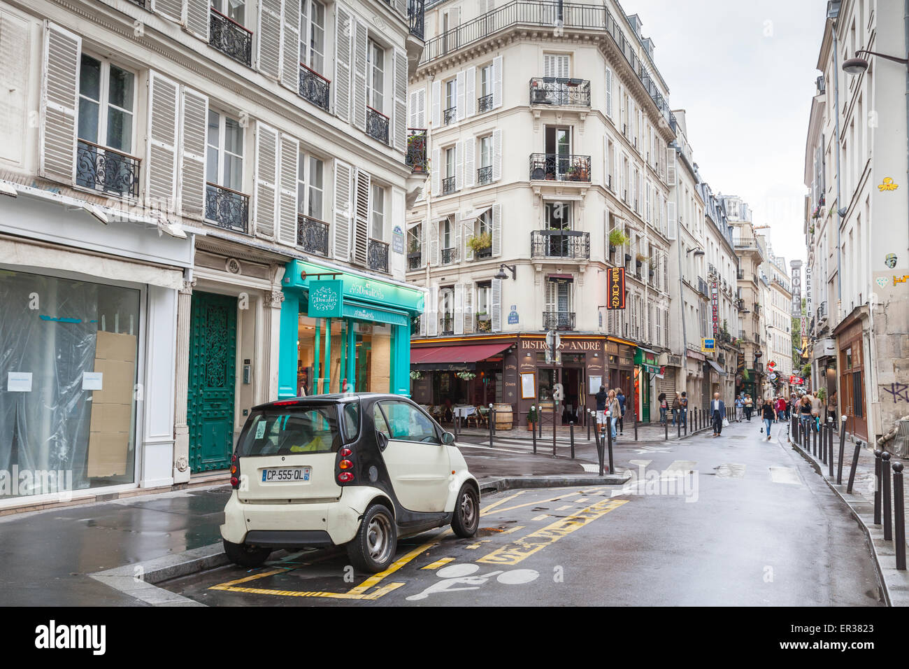 Paris, France - August 10, 2014: small white Smart car stands on the street in Paris, tourists walk on Rue St. Andre Stock Photo