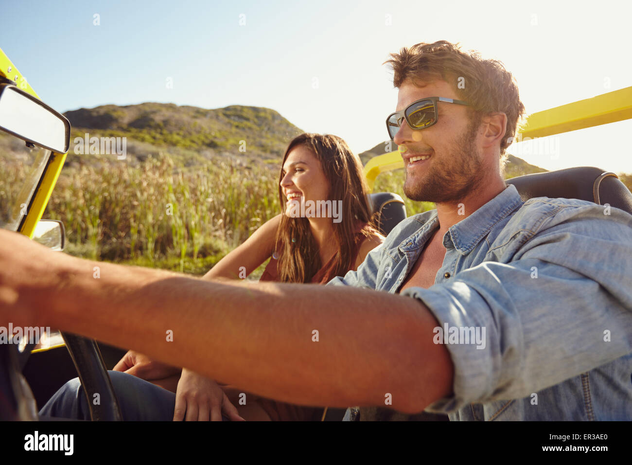 Young friends out for a drive together in a open topped car. Couple on road trip in a car. - Stock Image