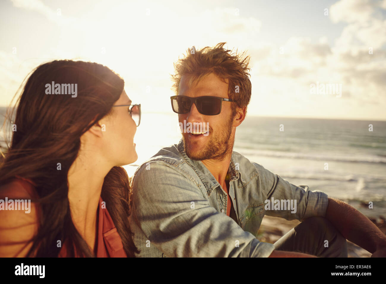 Close-up portrait of loving young couple looking at each other at the beach. Romantic caucasian couple in love on - Stock Image