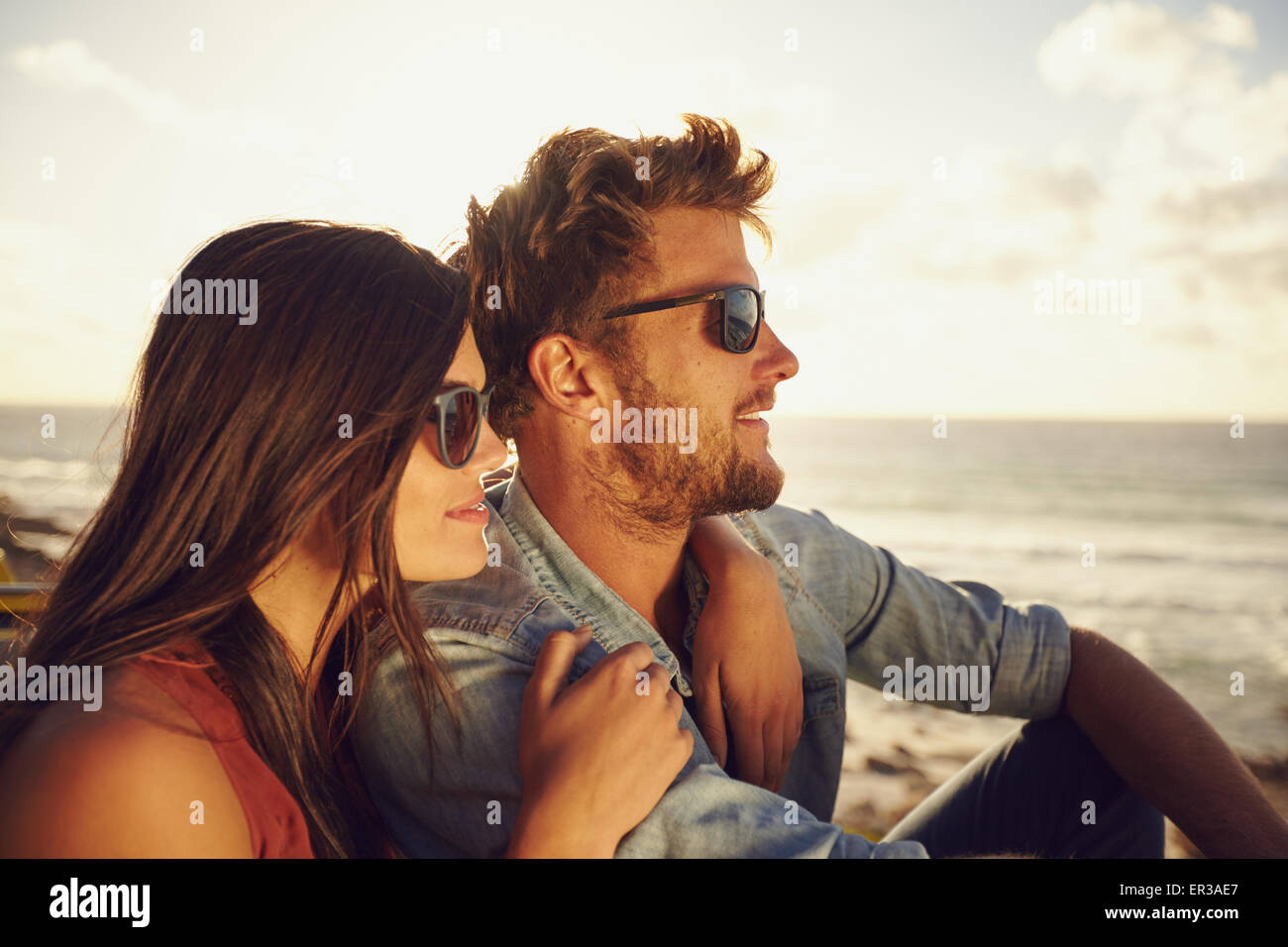 Beautiful young couple together outdoors on a summer day. Caucasian couple enjoying the beach view, both wearing - Stock Image
