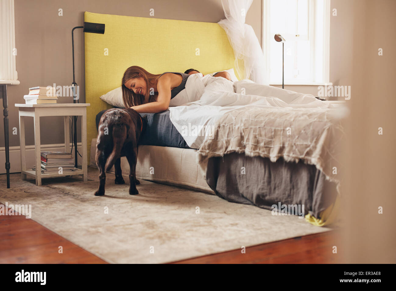 Woman lying on bed playing with her pet dog in morning. Man sleeping in background. - Stock Image