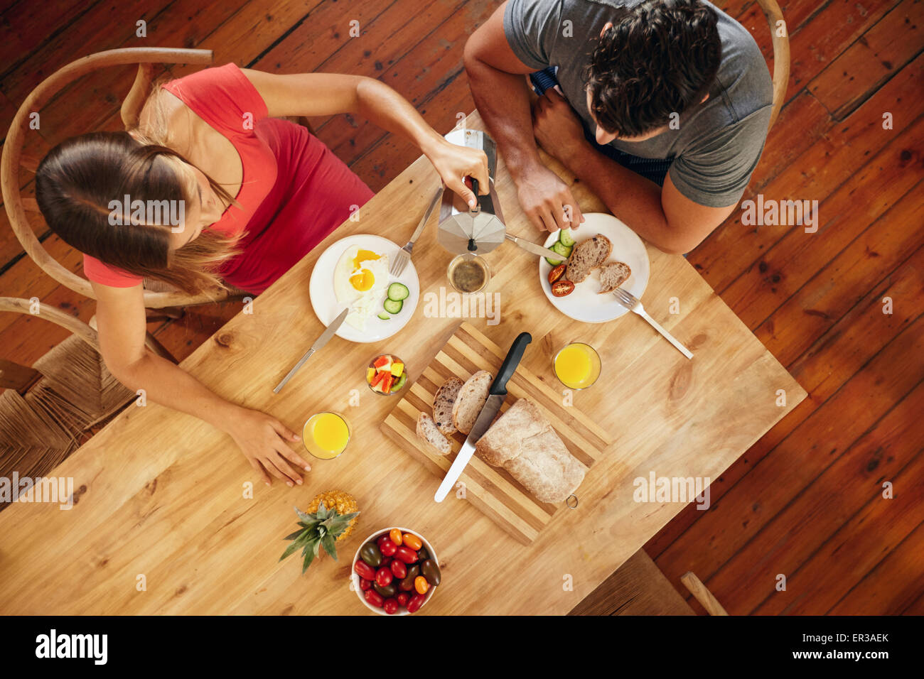 Overhead view of couple having morning breakfast in kitchen with woman serving coffee to man. - Stock Image