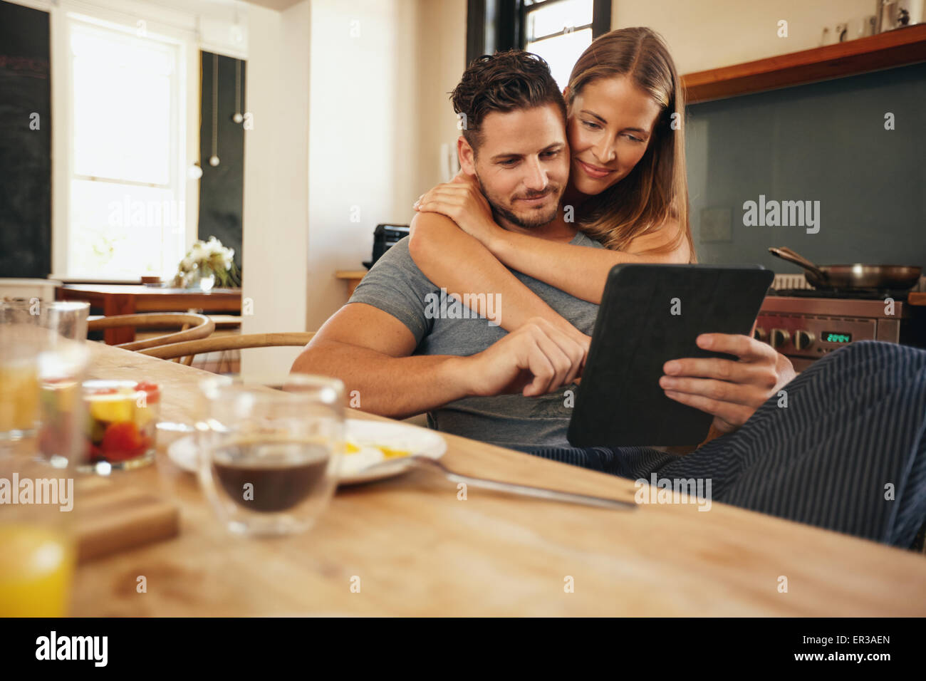 Indoor shot of young caucasian couple in the kitchen in the morning and using a digital tablet together. - Stock Image