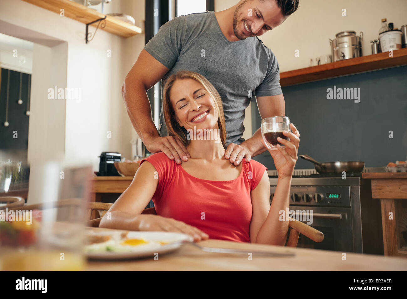 Happy young woman sitting at breakfast tablet holding cup of coffee getting a shoulder massage from her boyfriend. - Stock Image
