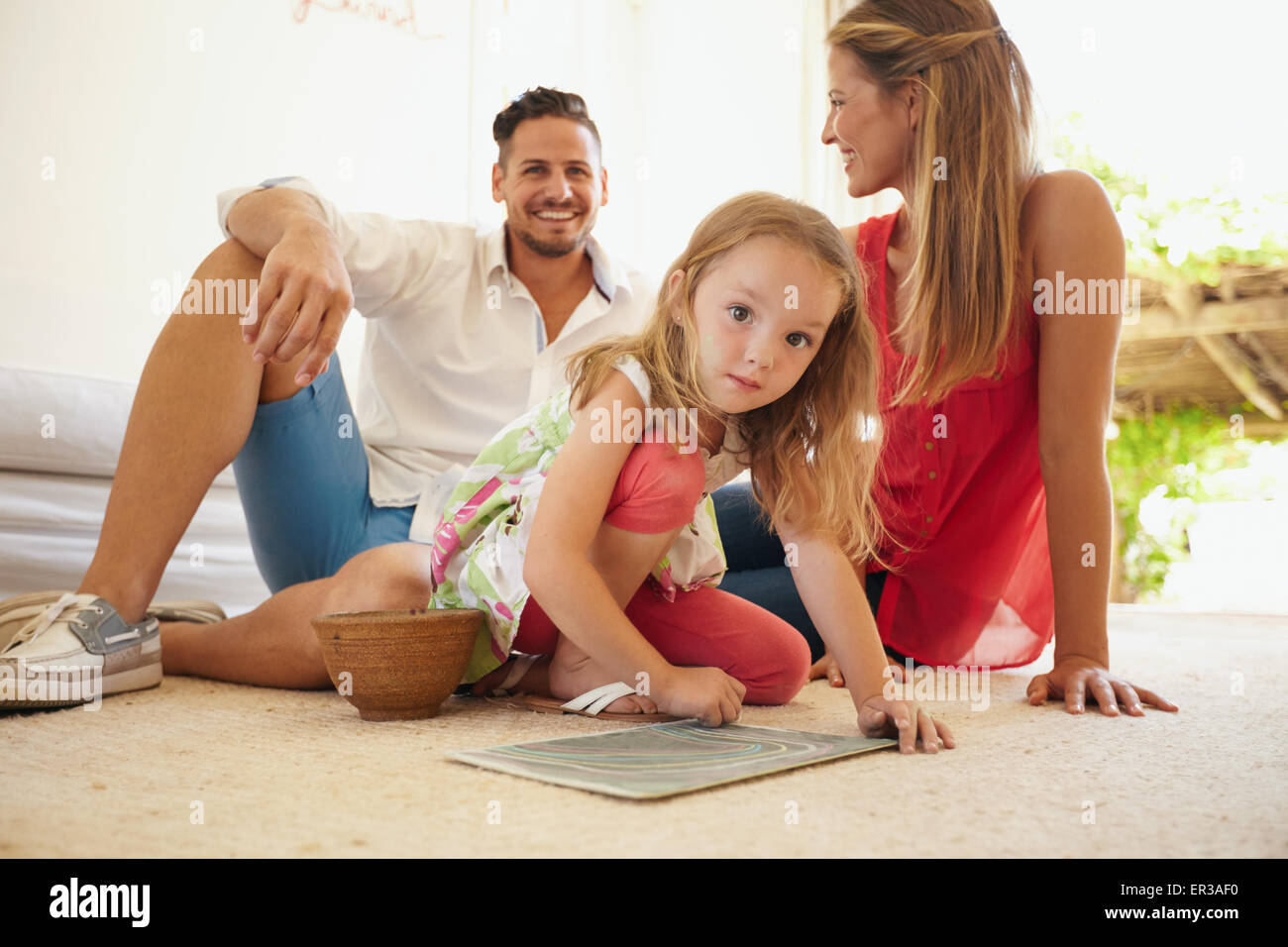 Indoor shot of cute little girl painting with her parents sitting behind her. Family sitting on floor in living - Stock Image