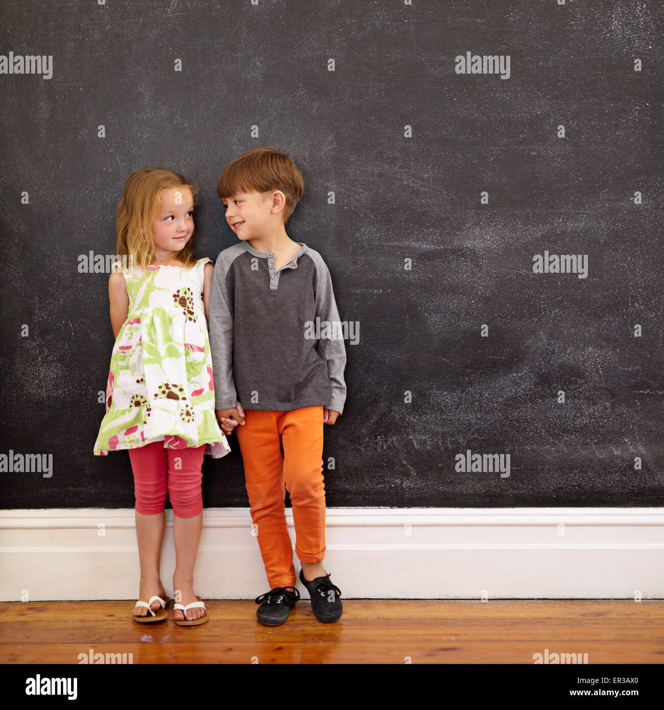 Little boy and girl standing in front of blackboard looking at each other. Indoors shot of children at home with - Stock Image