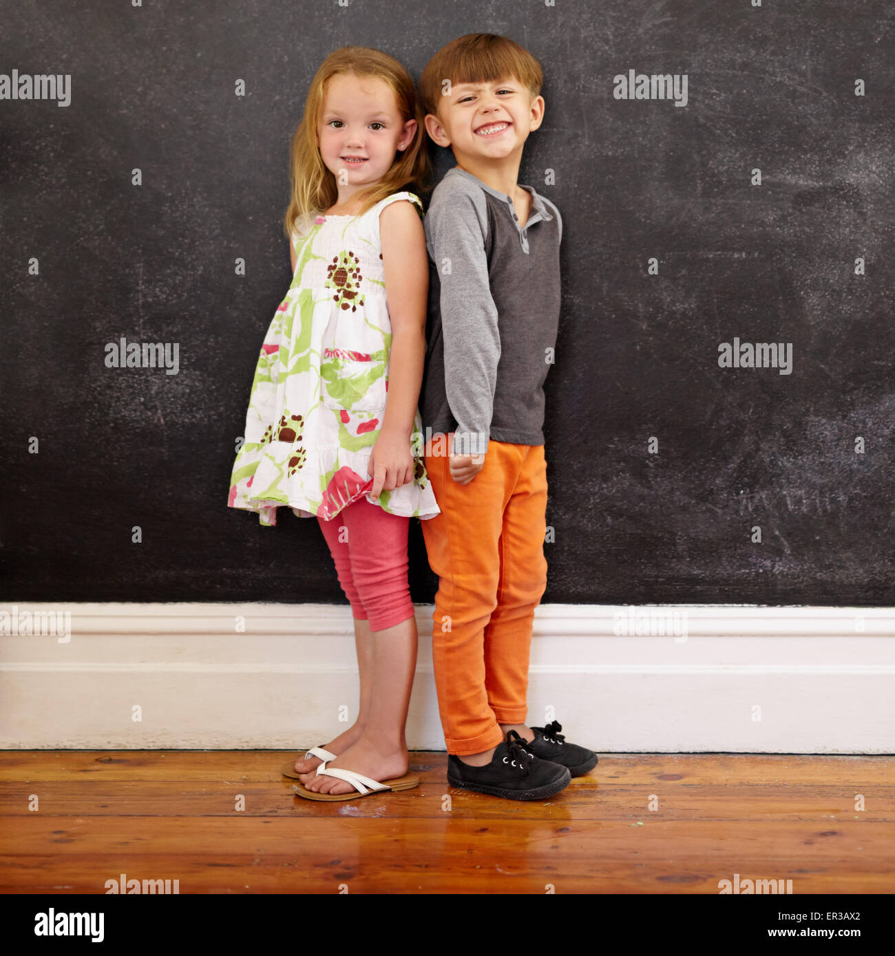 Little boy and girl standing back to back in front of blackboard looking at camera smiling. Full length image of - Stock Image