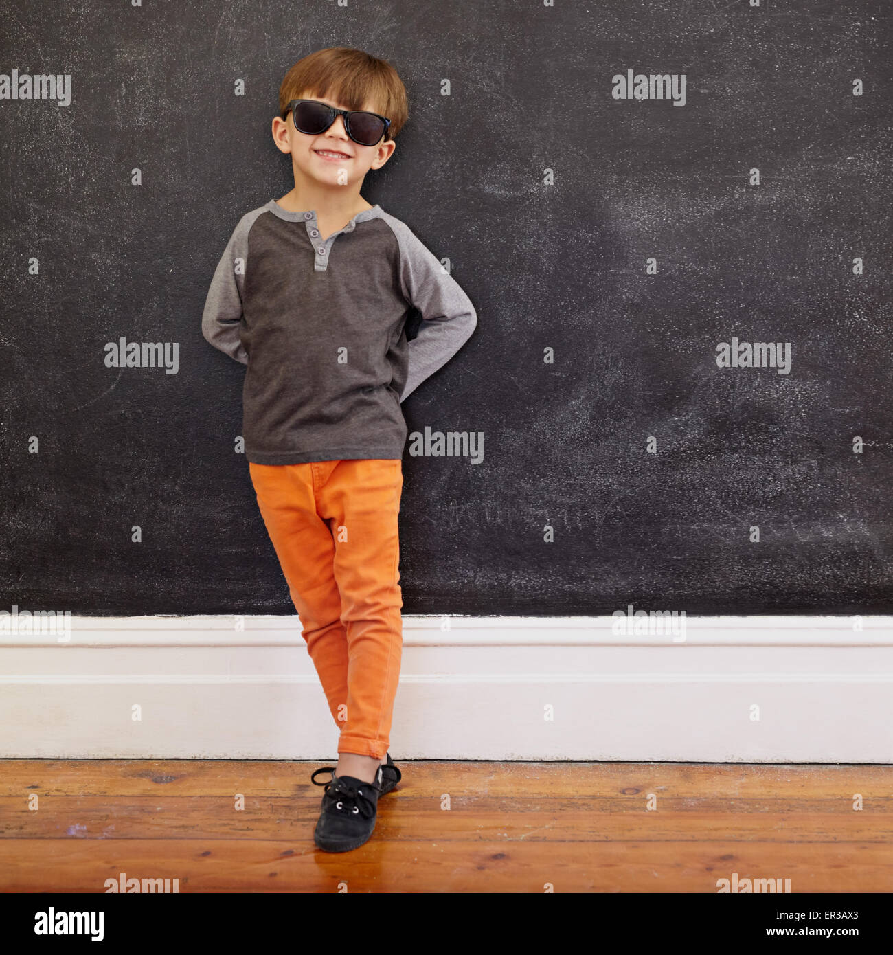 Full length shot of stylish little boy standing in front of the blackboard. Caucasian kid wearing sunglasses  posing - Stock Image