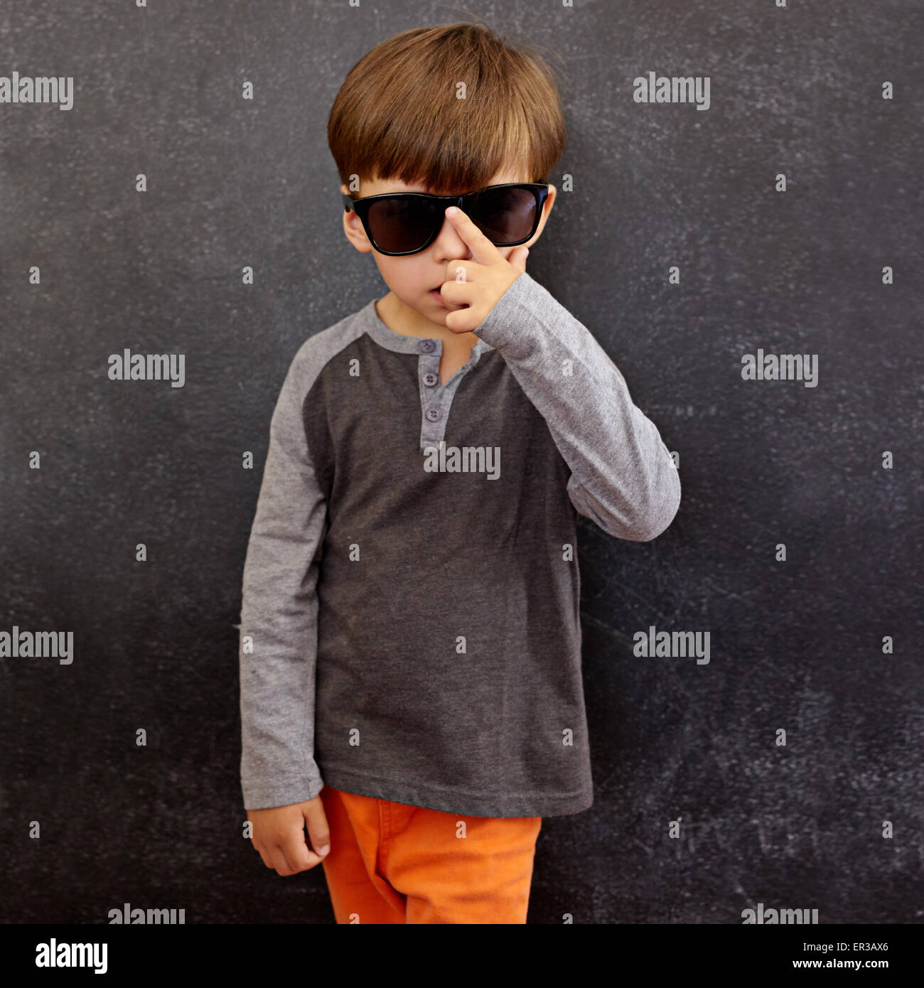 Portrait of little boy wearing sunglasses looking at camera. Small kid in front of a blackboard adjusting his shades. - Stock Image