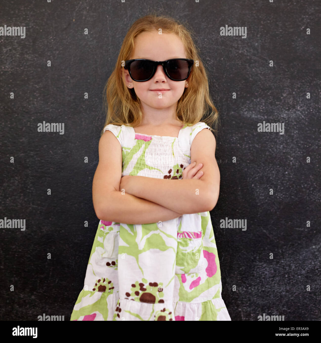 a446248a8b Portrait of cute little girl wearing sunglasses against a black wall. Young  girl standing in shades with her hands folded.