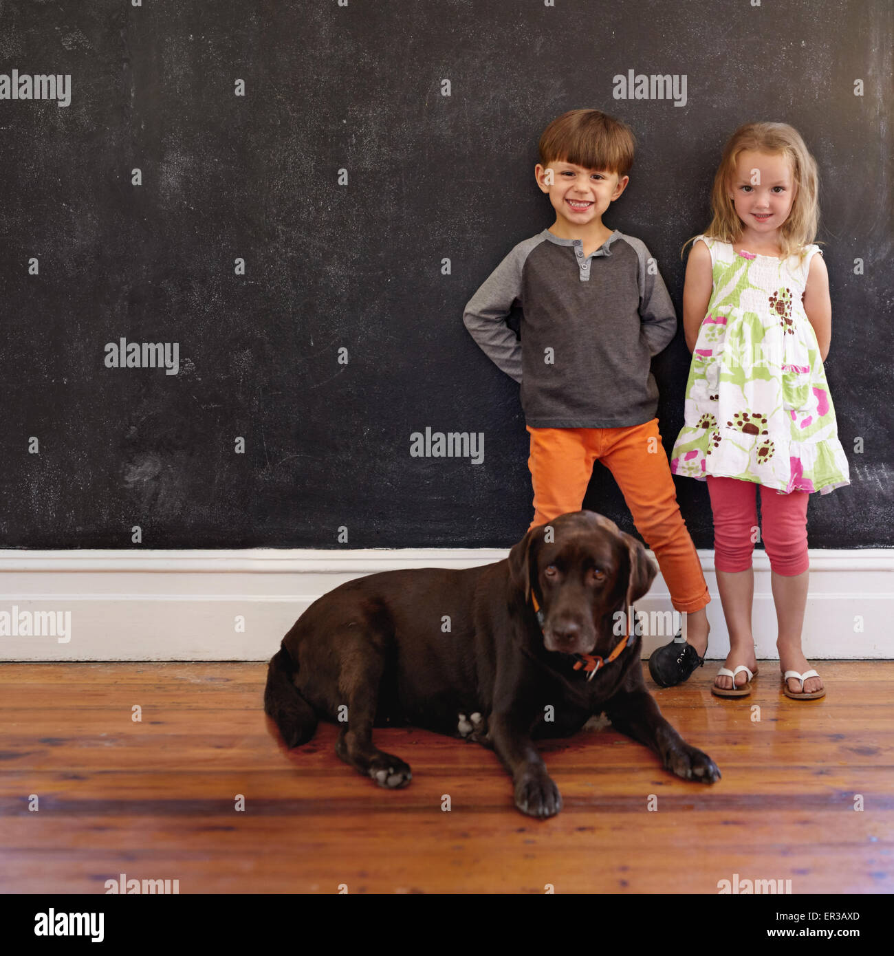 Full length shot of smiling little boy and girl standing next to dog at home. Labrador retriever sitting on floor - Stock Image