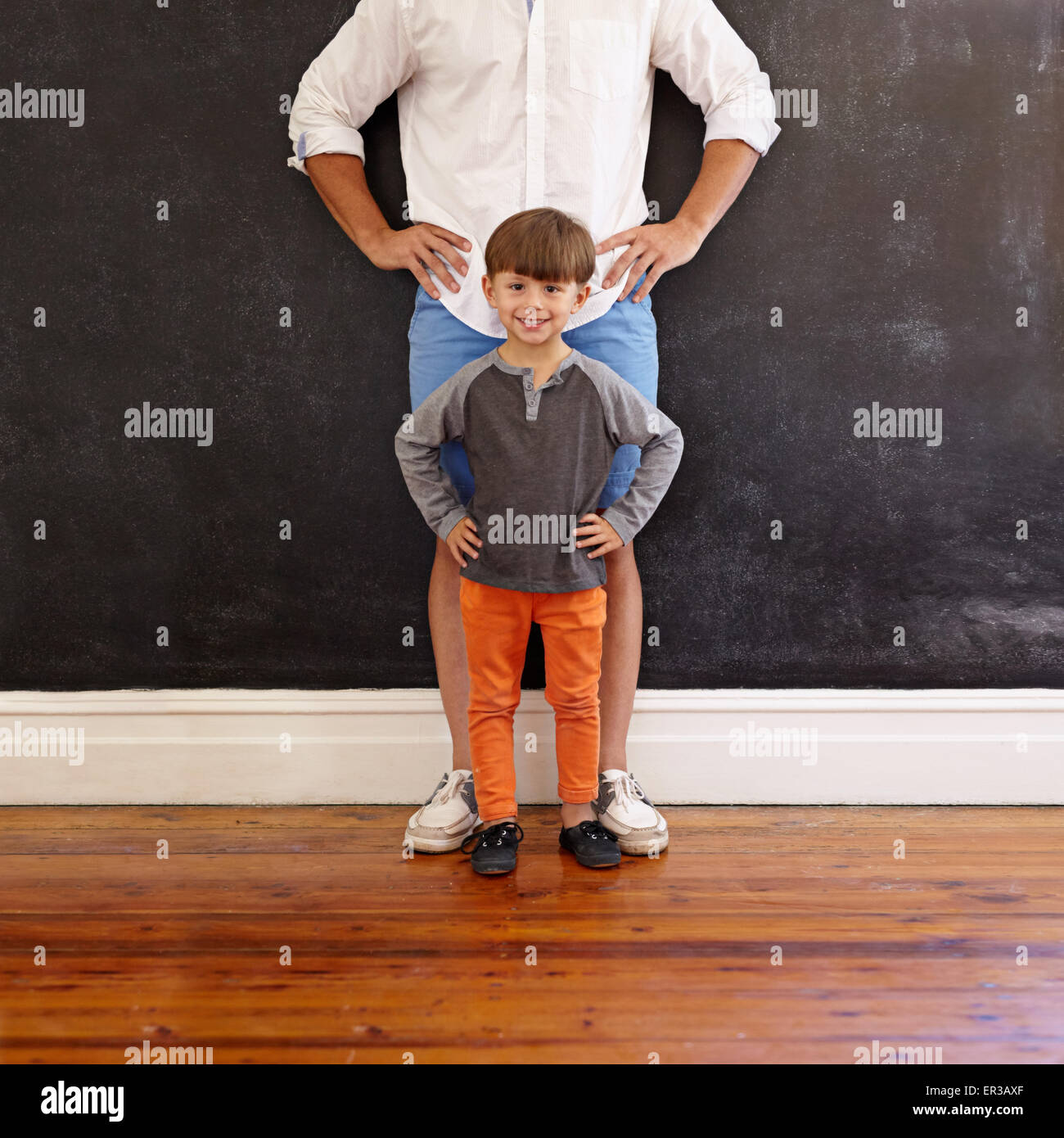 Indoor shot of little boy and his father standing with their hands on hips. Little boy in front smiling and his - Stock Image