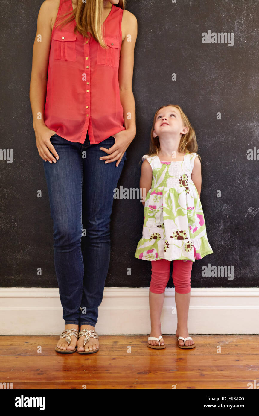 Cropped shot of woman with her daughter. Little girl looking at her mother standing by a black wall at home. - Stock Image