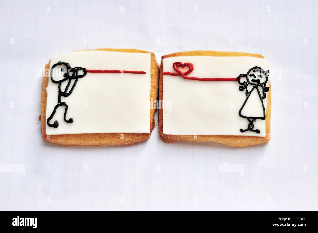 Cheese cracker with drawings of a girl talking to a boy using tin can telephone - Stock Image