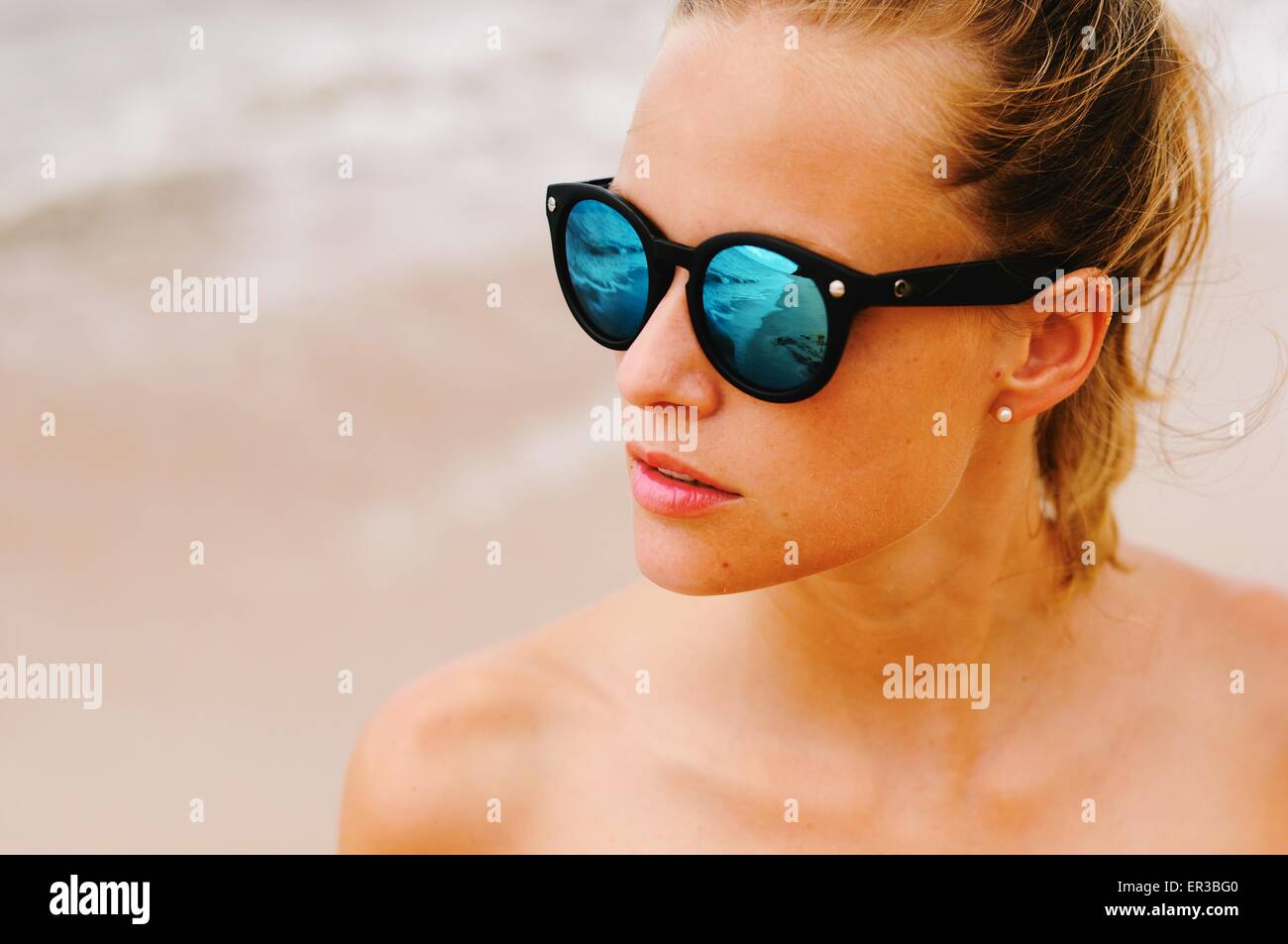Portrait of a woman at beach wearing sunglasses - Stock Image