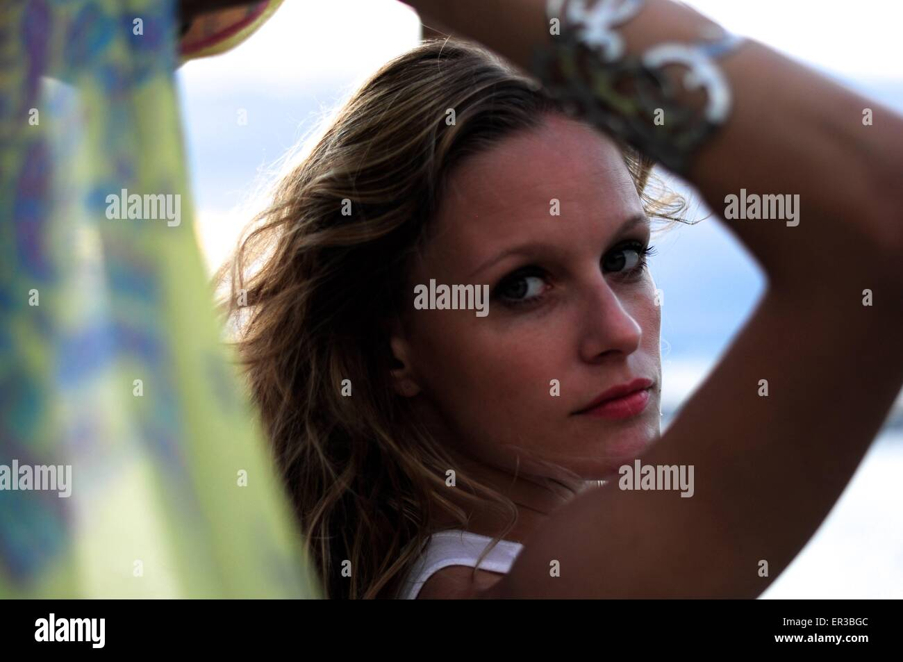 Woman looking over her shoulder - Stock Image