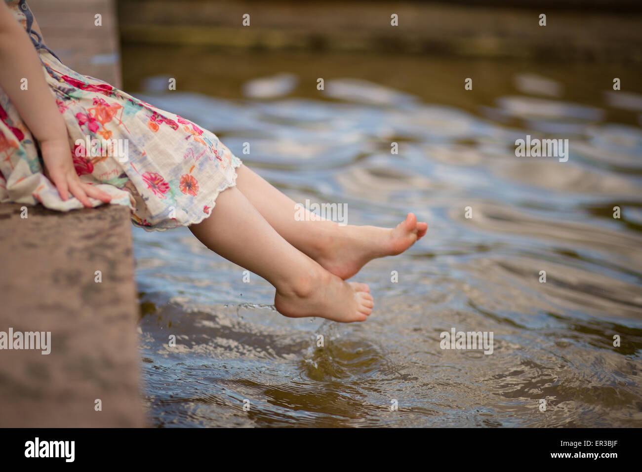 Girl dipping her feet in water - Stock Image