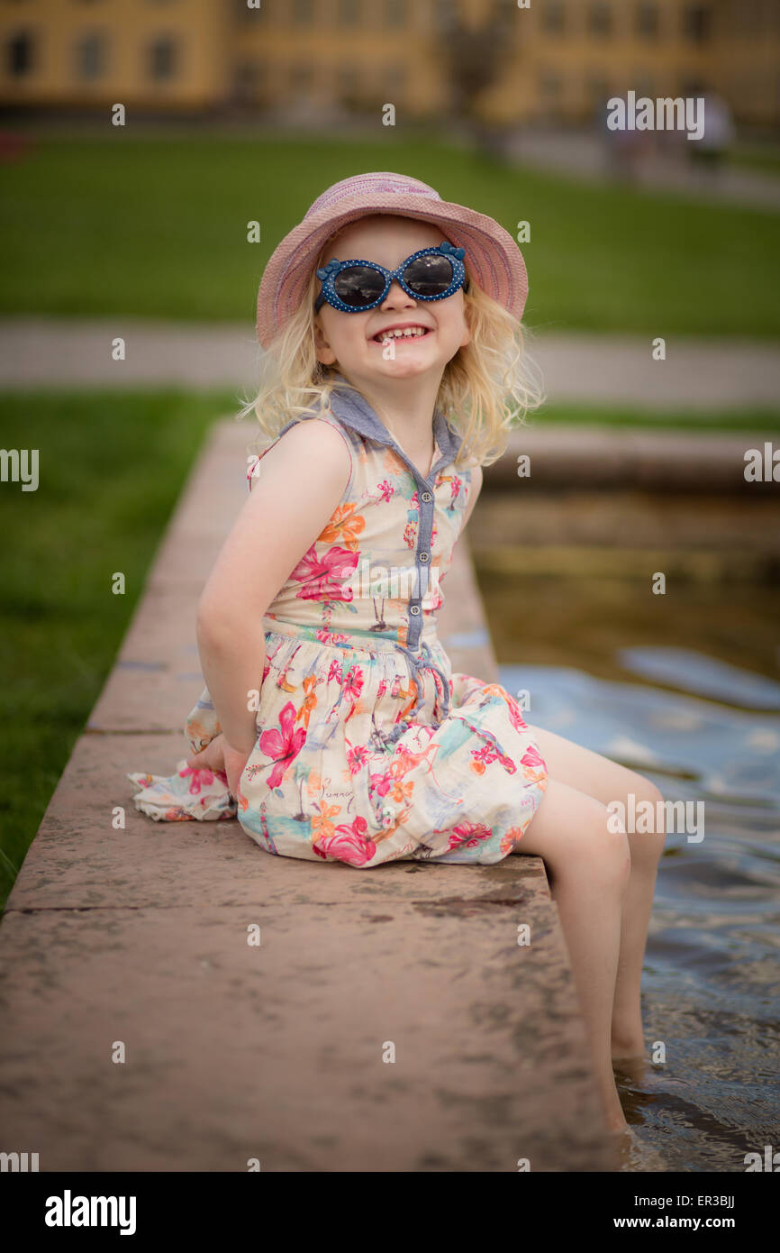 Girl sitting with her feet in water making a face - Stock Image