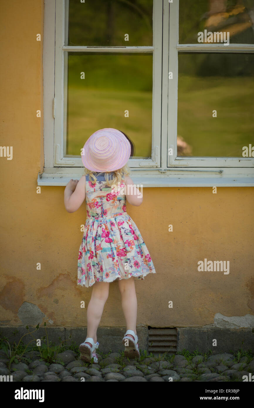 Rear view of a girl looking through a window - Stock Image