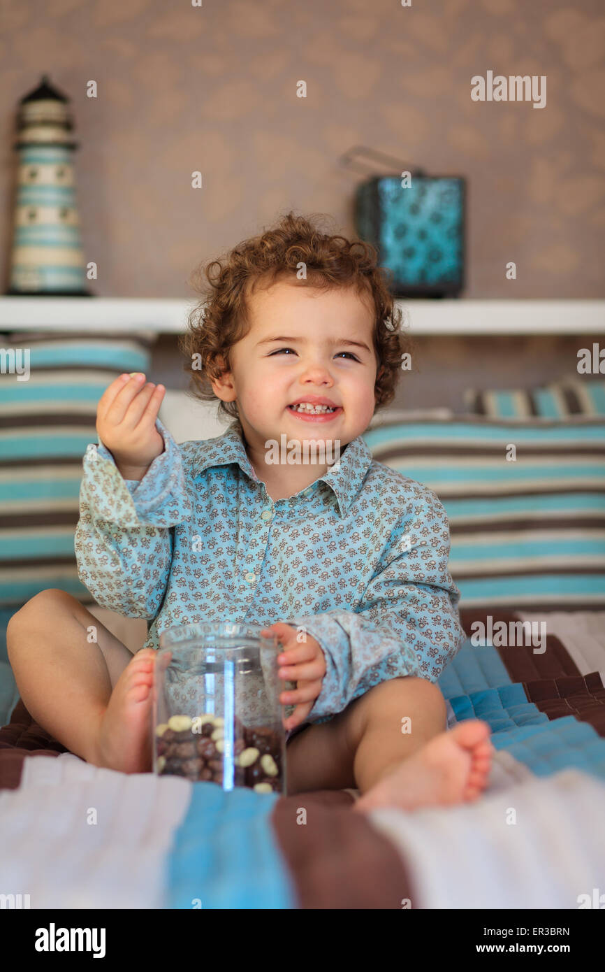Smiling girl sitting on the bed eating sweets - Stock Image