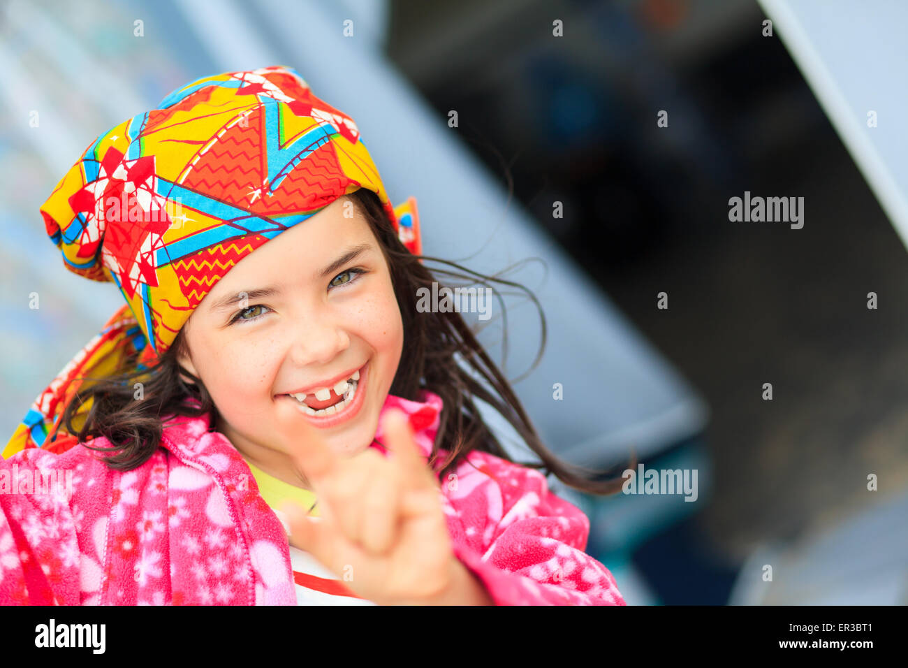Portrait of a smiling girl gesturing horn sign - Stock Image
