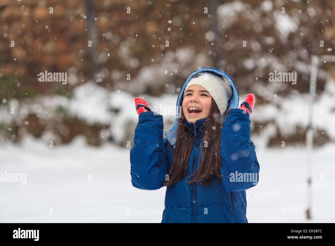 Girl with her hands in the air playing in the snow - Stock Image