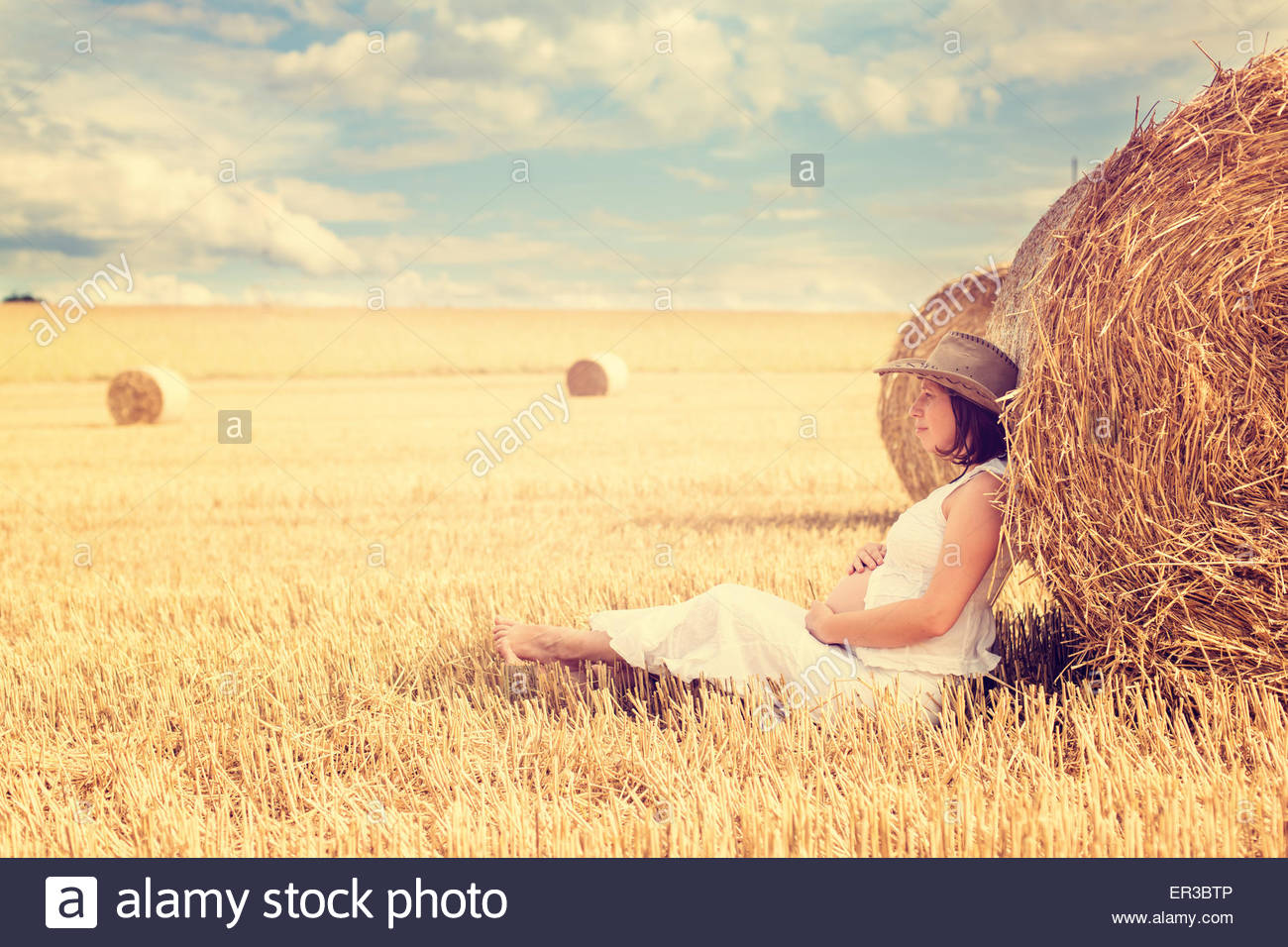 Pregnant woman leaning against a hay bale in a field - Stock Image