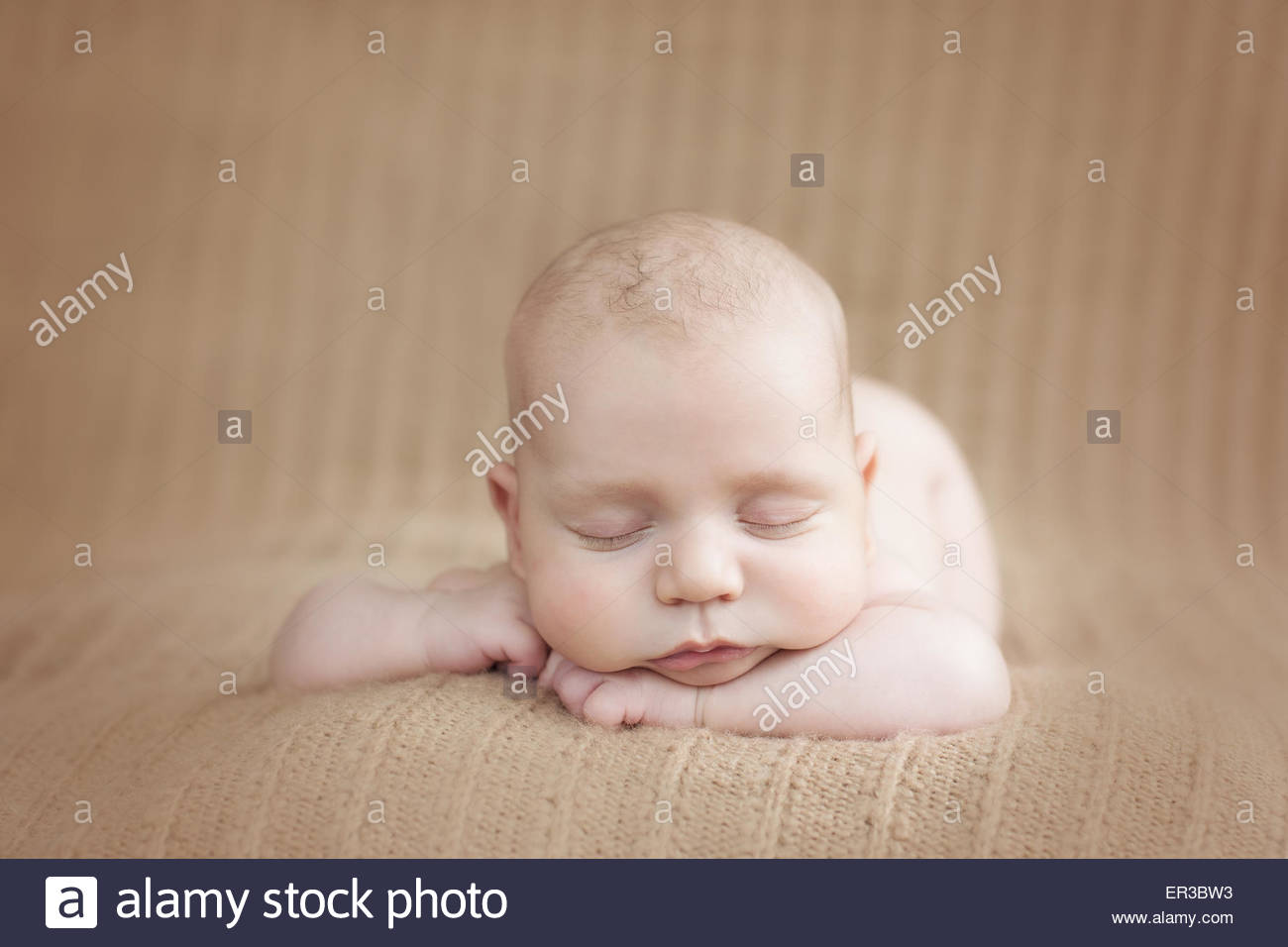 Front view of a baby boy sleeping on a soft blanket - Stock Image