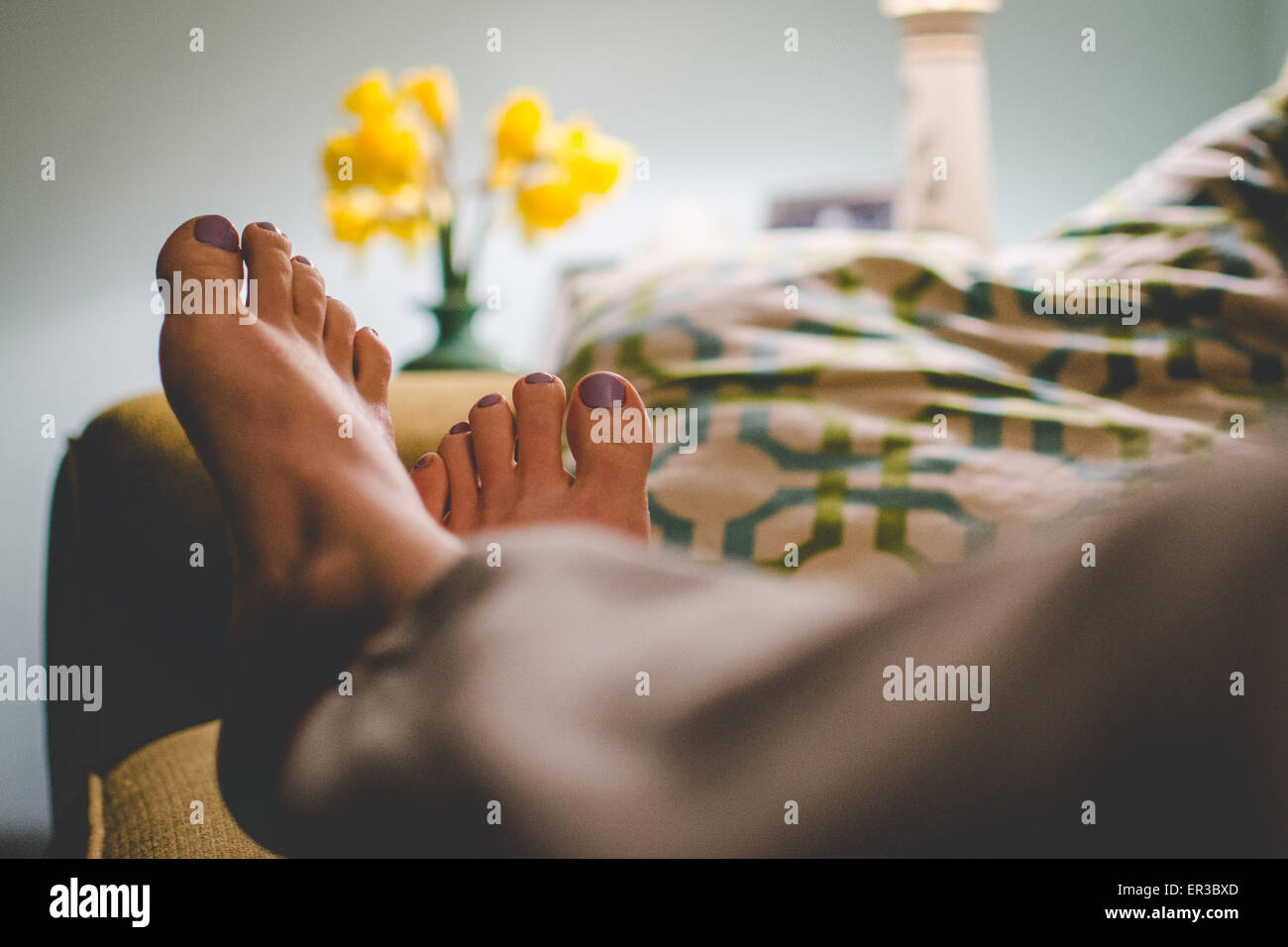 Woman's feet as she relaxes on the couch in the evening - Stock Image