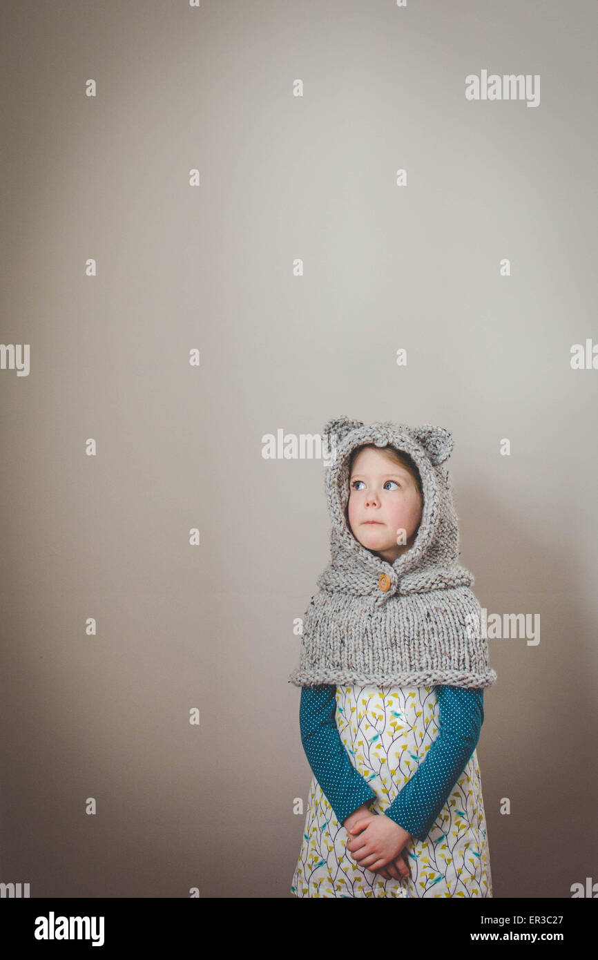 Portrait of a girl wearing a knitted cowl with bear ears looking up - Stock Image