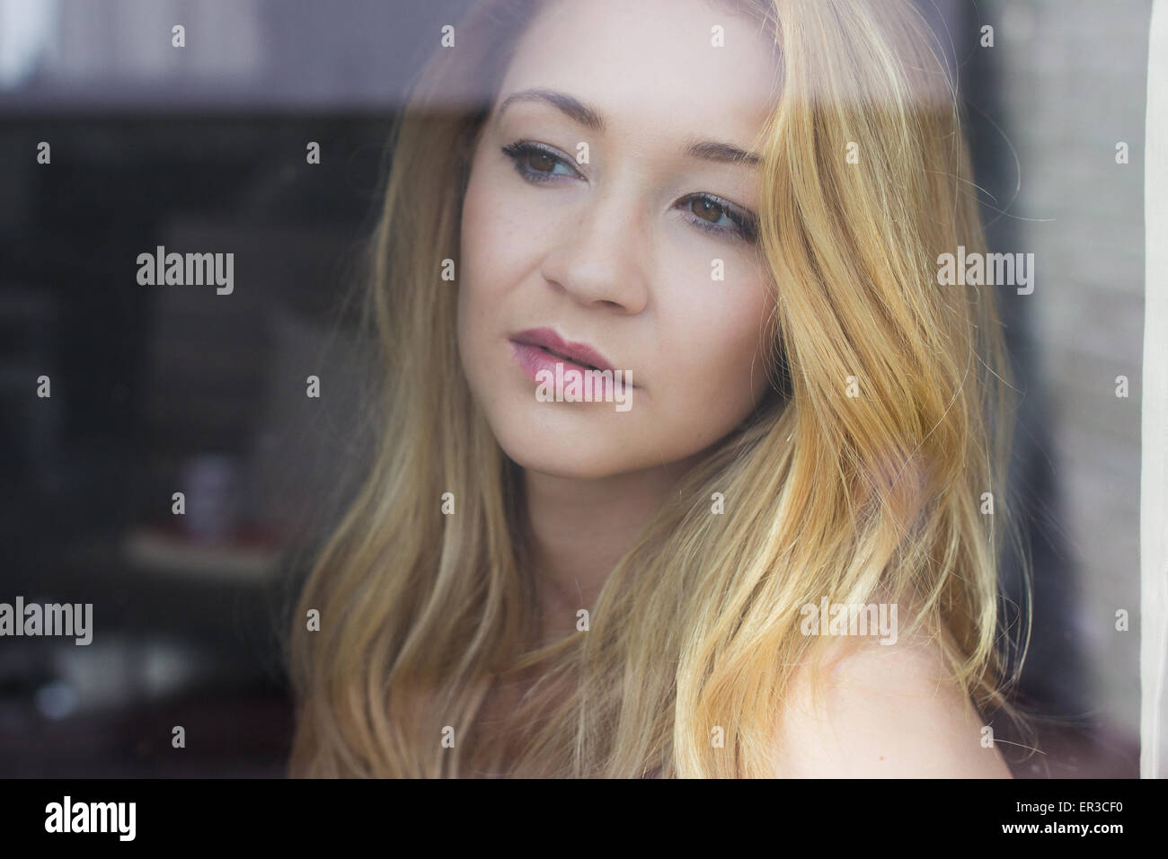 Portrait of a young woman looking out of the window - Stock Image