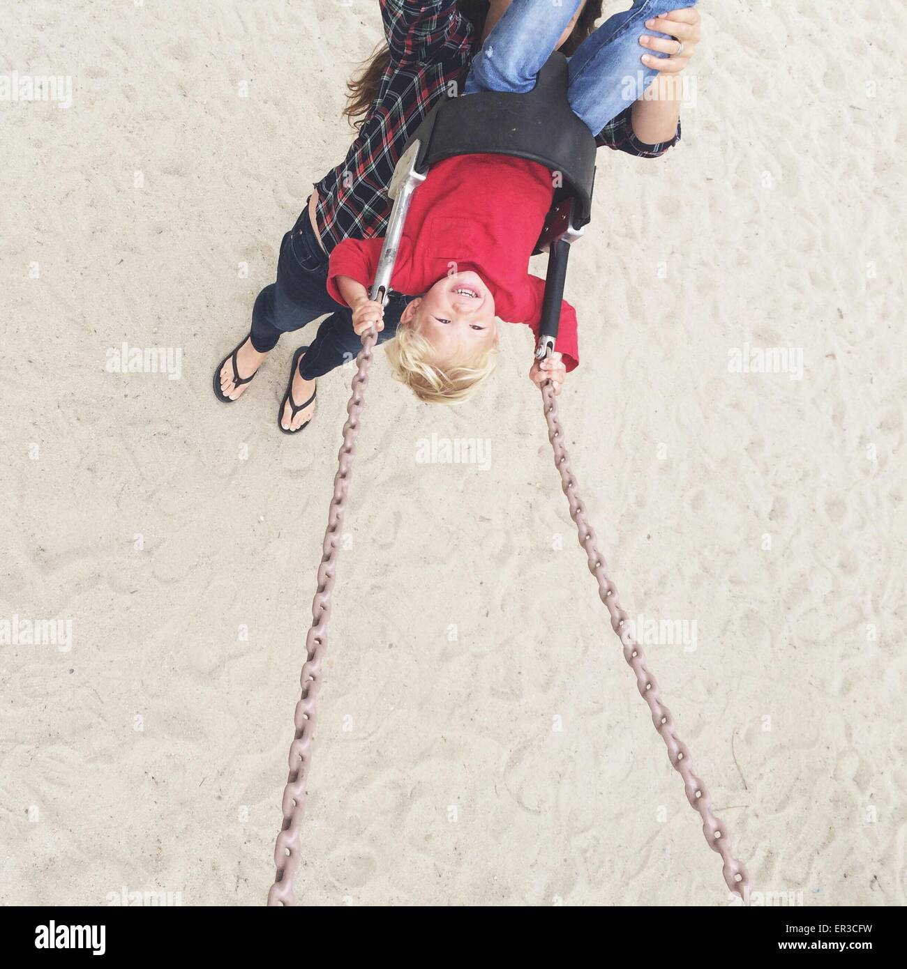 Elevated view of a woman pushing her son on a swing - Stock Image