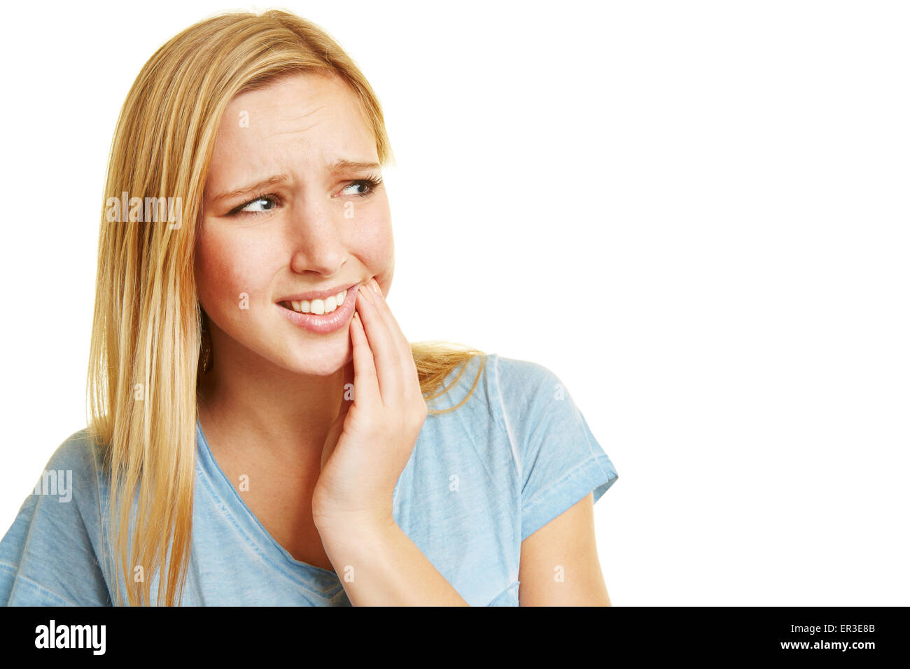 Young woman with toothache holding hand to her mouth - Stock Image