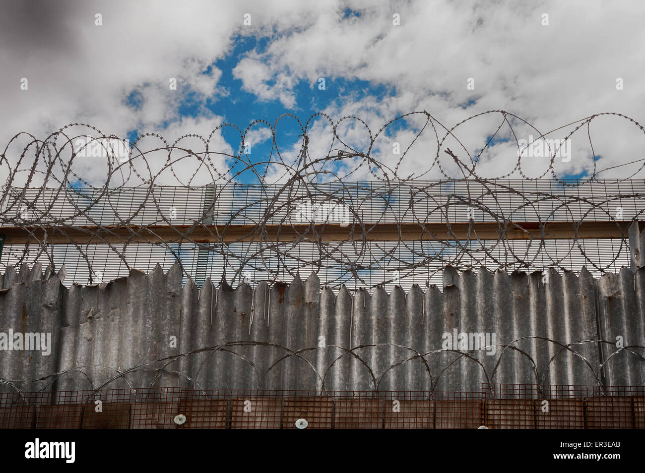 Galvanised high security razor wire and barbed wires deterrent to slow down climbing over walls with mass of corrugated - Stock Image
