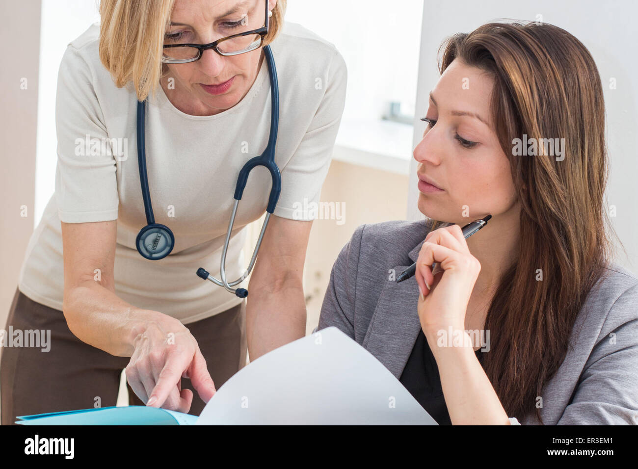 A medical secretary receives instructions from the doctor she assists. - Stock Image
