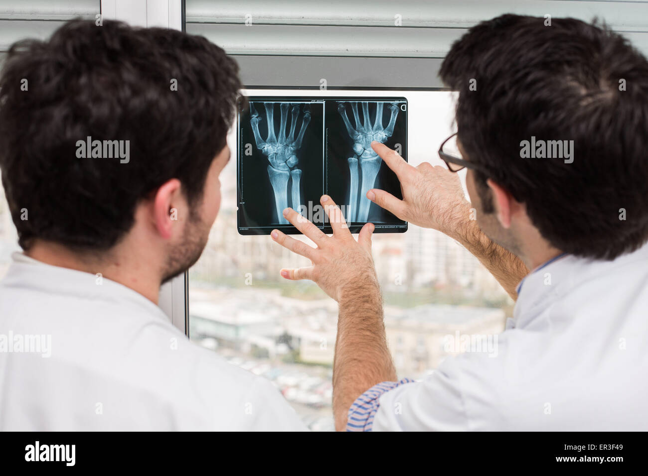 Rheumatologist (right) and internal examining radiographs of the hands of a patient with rheumatoid arthritis, Bordeaux - Stock Image